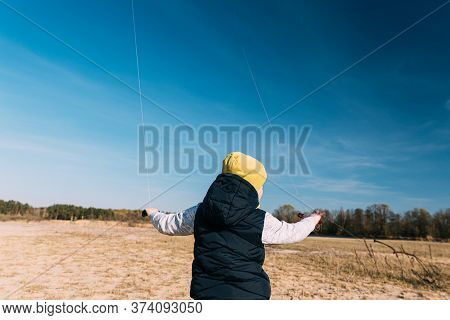Caucasian Boy Of 6-7 Years Old Keep Two Twines From A Kites. Pleasant Activity In Fresh Air On A Sun