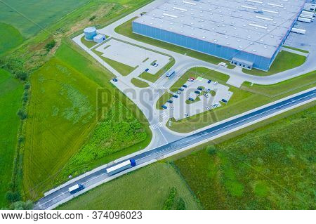 Aerial View Of Goods Warehouse. Logistics Center In Industrial City Zone From Above. Aerial View Of