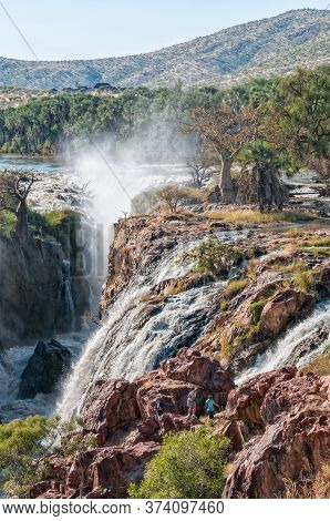 Epupa, Namibia - May 24, 2011: Part Of The Epupa Waterfalls In The Kunene River. People, Baobab And