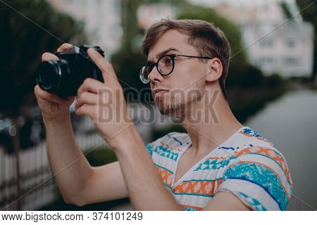Young Cheerful Man Photographer Taking Photographs With Digital Camera