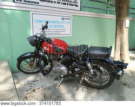 Closeup Of Maroon Or Red Color Royal Enfield Bike Parking Near Building Office Compound