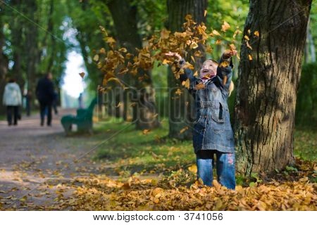 Girl And Leaves At Autumn