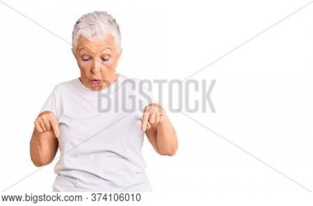 Senior beautiful woman with blue eyes and grey hair wearing casual white tshirt pointing down with fingers showing advertisement, surprised face and open mouth