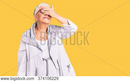 Senior beautiful woman with blue eyes and grey hair wearing casual clothes and glasses smiling and laughing with hand on face covering eyes for surprise. blind concept.