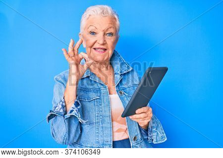 Senior beautiful woman with blue eyes and grey hair using touchpad device doing ok sign with fingers, smiling friendly gesturing excellent symbol