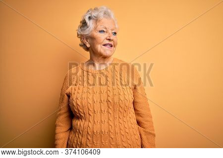 Senior beautiful grey-haired woman wearing casual sweater over isolated yellow background looking away to side with smile on face, natural expression. Laughing confident.