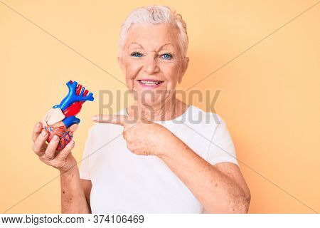 Senior beautiful woman with blue eyes and grey hair holding heart organ smiling happy pointing with hand and finger