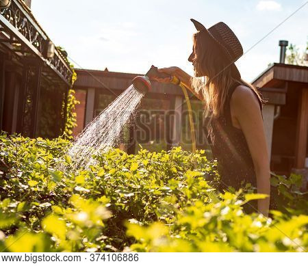 Pretty Young Girl In A Hat Watering Plants With A Garden Hose In The Garden In Summer, Photography F