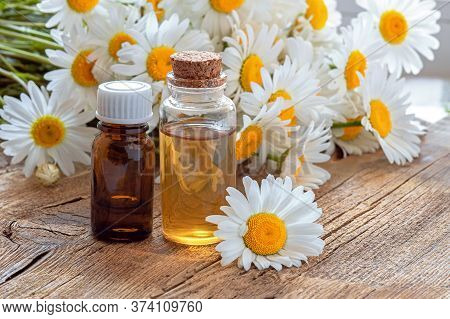 Bottles Of Essential Oil And Chamomile Flowers On Wooden Table. Essential Oil In A Glass Bottle With