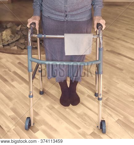 Old Wrinkled Hands On Walking Frame. Hands Of A Standing Senior Woman Leaning On A Rollator. Pension