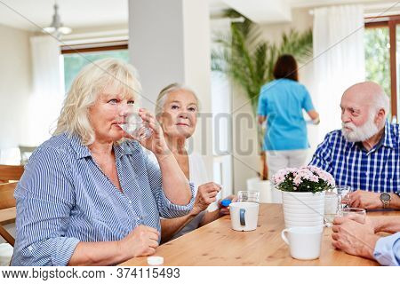 Senior citizens in the old people's home are waiting for medication or taking medicine
