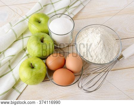 Raw Ingredients Prepared For Baking Apple Pie: Sour Green Apples, Wheat Flour, Sugar And Eggs On A W