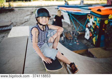Trendy Skateboarder Enjoying Free Time At Skate Park, Sitting On Half Pipe Ramp. Resting After Skate