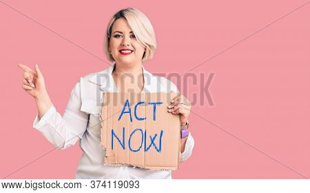 Young blonde plus size woman holding act now cardboard banner smiling happy pointing with hand and finger to the side