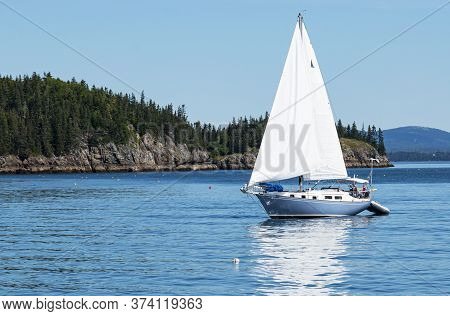 A Light Blue Sailboat Is Sailing Peacefully In Frenchman Bay Around The Porcupine Islands In Bar Har