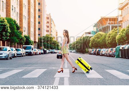 Young Woman Across The Street With A Yellow Suitcase