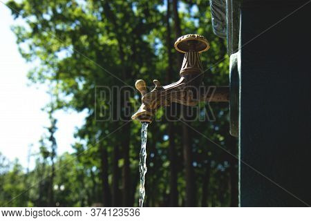 Open Beautiful Vintage Water Tap In A Park In In Hot Summer. A Faucet With A Pouring Water. Economic