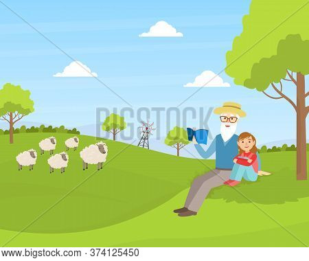 Grandfather With Granddaughter Sitting On Green Lawn And Reading Book, Grandparent And Grandchild Ha