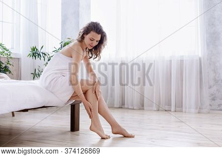 Happy Pretty Girl Enjoying Her Silky Skin After Shower At Home, Touching Her Legs, Copy Space