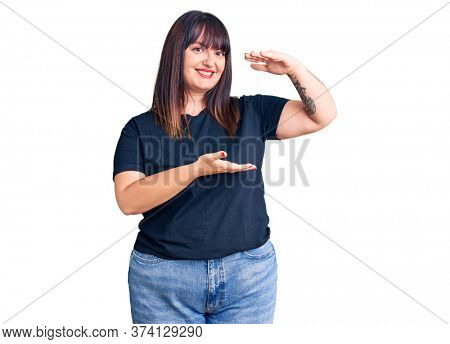 Young plus size woman wearing casual clothes gesturing with hands showing big and large size sign, measure symbol. smiling looking at the camera. measuring concept.