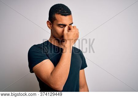 Young handsome african american man wearing casual t-shirt standing over white background tired rubbing nose and eyes feeling fatigue and headache. Stress and frustration concept.