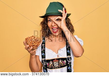 Middle age woman wearing traditional octoberfest dress holding bowl with baked pretzels with happy face smiling doing ok sign with hand on eye looking through fingers