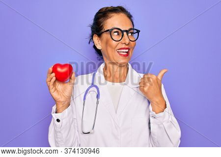Middle age senior cardiologist doctor woman holding red heart over purple background pointing and showing with thumb up to the side with happy face smiling