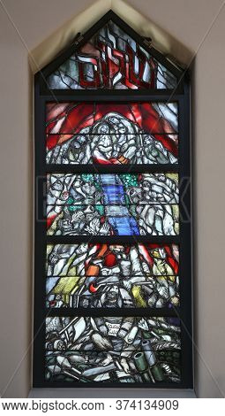 PIFLAS, GERMANY - JUNE 07, 2015: God bears the guilt of all mankind, takes hold of sinners and saves them from death, stained glass window by Sieger Koder in St. John church in Piflas, Germany