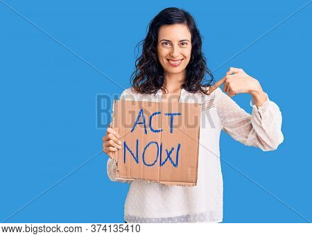 Young beautiful hispanic woman holding act now banner pointing finger to one self smiling happy and proud