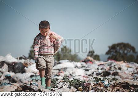 A Poor Boy Collecting Garbage Waste From A Landfill Site In The Outskirts .  Children Work At These