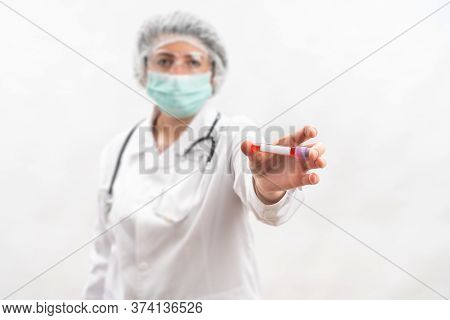 Medic Nurse On A White Background, Shows Compares, Test Tube With Virus Bacteria.