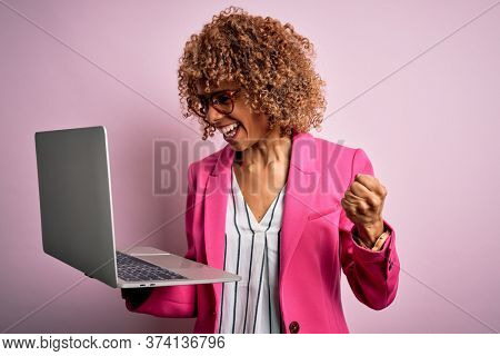 African american business woman with curly hair working using laptop over pink background screaming proud and celebrating victory and success very excited, cheering emotion