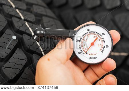 Close Up Picture Of Black New Car Tyre And Mechanic\'s Hand Next To