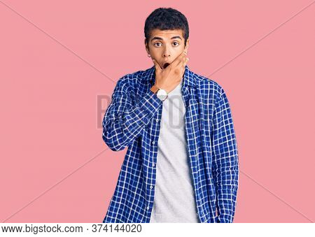 Young african amercian man wearing casual clothes looking fascinated with disbelief, surprise and amazed expression with hands on chin