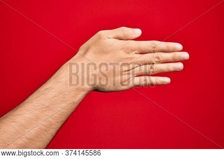 Hand of caucasian young man showing fingers over isolated red background stretching and reaching with open hand for handshake, showing back of the hand