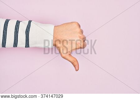 Hand of caucasian young man showing fingers over isolated pink background doing thumbs down rejection gesture, disapproval dislike and negative sign