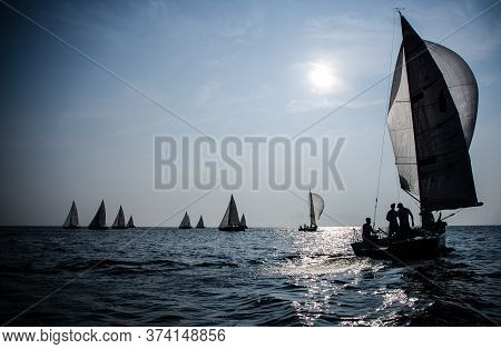 Sailing Yacht Race. Ship Yachts With White Sails In The Open Sea. Silhouettes Of Yachtsmen And Boats