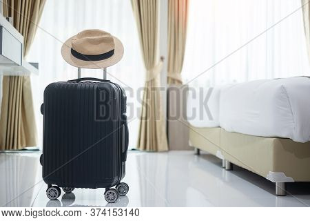 Black Luggage And Hat In Modern Hotel Room With Windows, Curtains And Bed. Time To Travel, Relaxatio