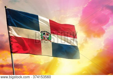 Fluttering Dominican Republic Flag On Beautiful Colorful Sunset Or Sunrise Background. Dominican Rep