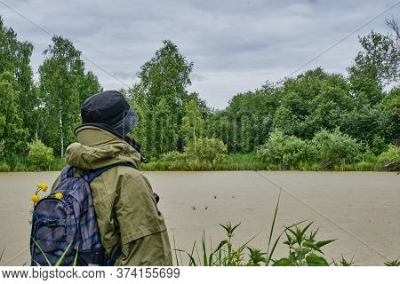 Active Man In Mosquito Suit With Backpack In Hiking Near Overgrown Taiga Lake In A Siberian Forest,