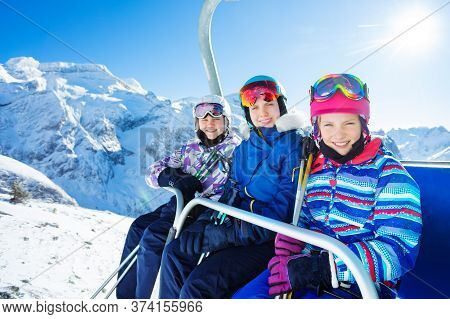 Group Of Three Smiling Teen Girls Sit On Chairlift Wearing Helmet And Bright Ski Outfit With Friends