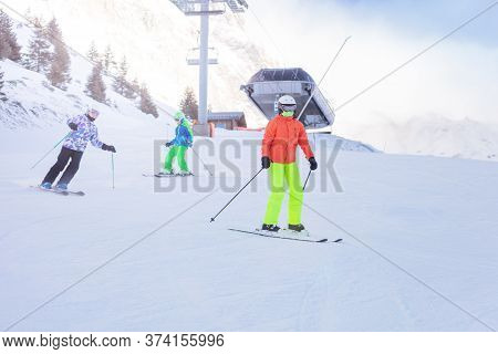 Three Children Ski Downhill Together In Colorful Outfit On Alpine Mountain Slope With Lift Station O