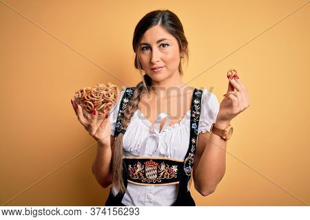 Young brunette german woman wearing traditional Octoberfest dress holding bowl with pretzels with a confident expression on smart face thinking serious