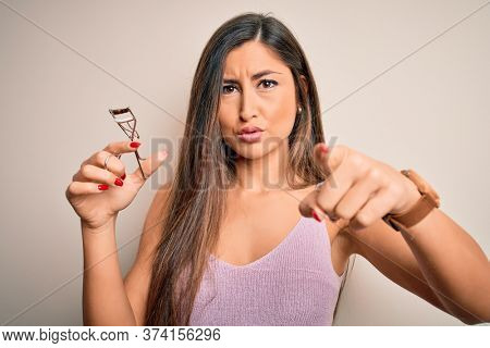 Young beautiful brunette woman holding eyelash curler over isolated white background pointing with finger to the camera and to you, hand sign, positive and confident gesture from the front