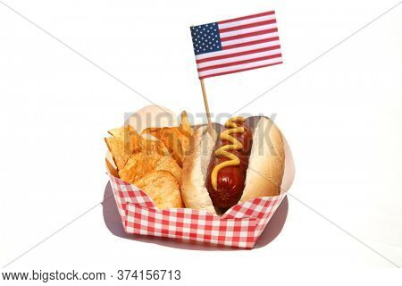Hot Dog. Hot Dog with Mustard, Potato Chips and an American Flag. Isolated on white. Room for text. Hot Dogs are a perfect meal for any Holiday Lunch. 4th of July Hot Dog and Potato Chips.