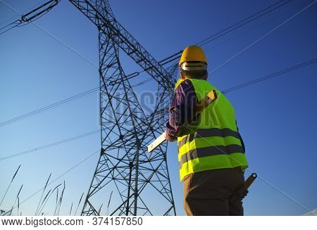 Engineer During Power Line Inspection. Electrician At Work. Production And Supply Of Energy From Pow