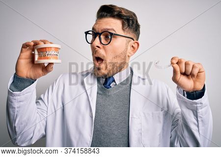 Professional dentist doctor holding denture with braces and invisible aligner, comparing healthy orthodontics teeth alignment looking suprised and amazed