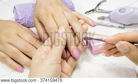 Manicure. Push Back The Cuticle With A Metal Pusher. Manicure Tools. Manicure Process In A Beauty Sa