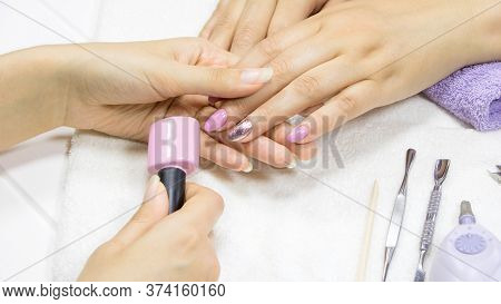 The Manicurist Shows The Client The Color Of Nail Polish. The Woman Chooses The Color Of The Gel Pol