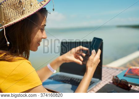 Side View Woman In Hat At Beach With Laptop, Using Smartphone, Online Chatting, Browsing On Internet